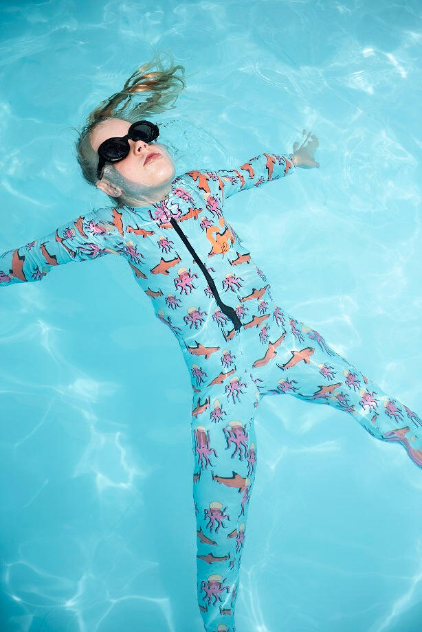 girl floating in pool wearing sunsuit swimwear