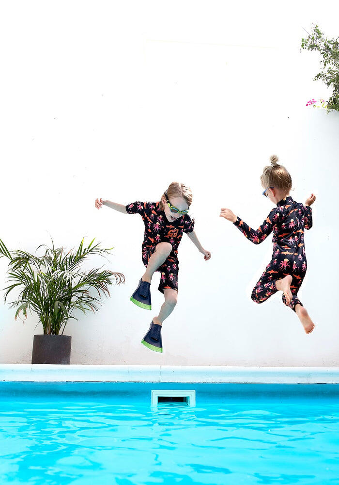 boys jumping into pool wearing sunsuit