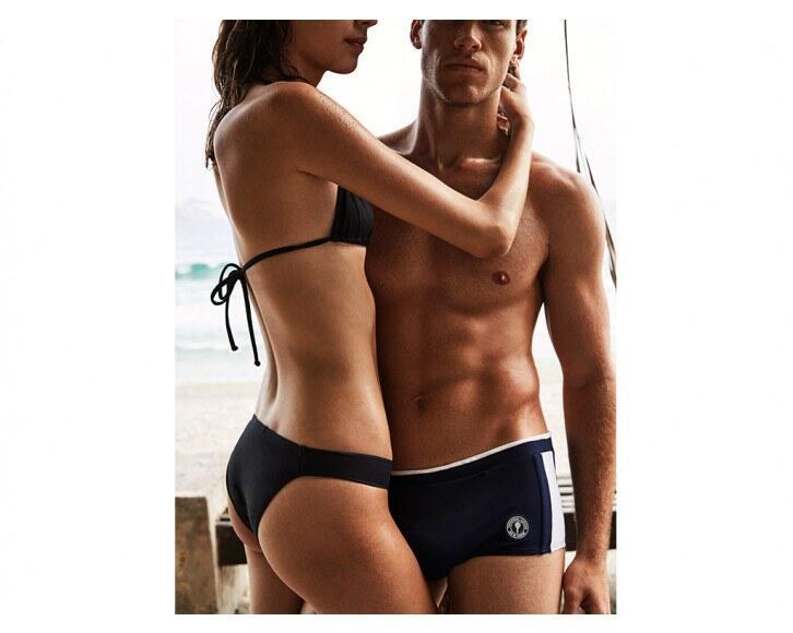 woman holding man in brazilian sungas