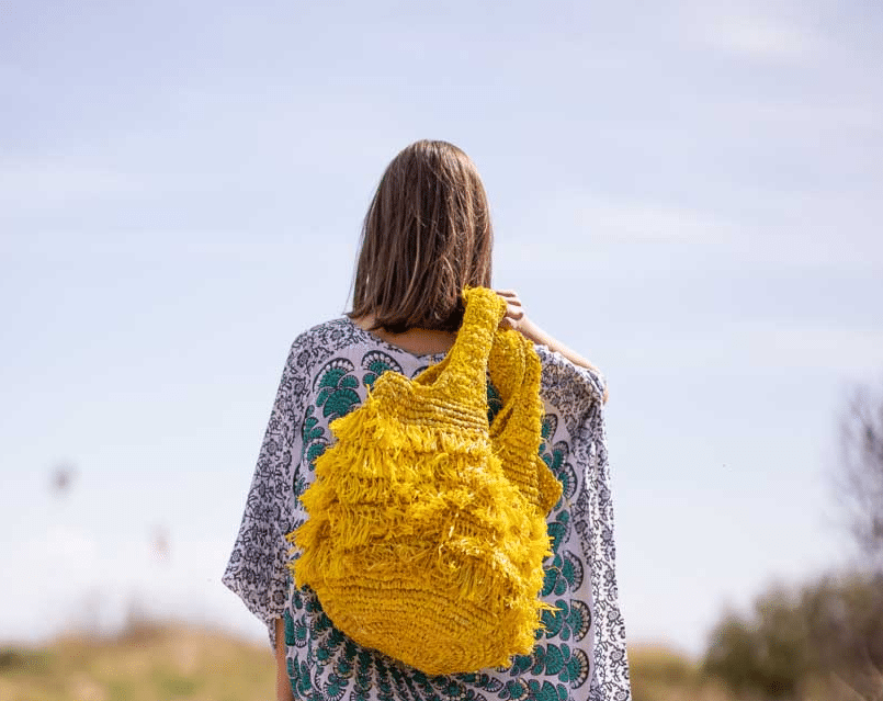 woman carrying a yellow hippie bag